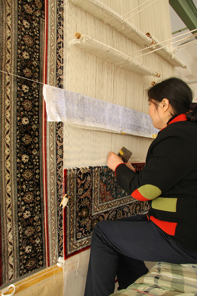 Silk rug weaving on a hand loom in Shanghai, China. Worker artisan is following a blueprint.
