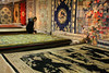 Silk rugs on display and for sale in Shanghai, China - with potential customer examining