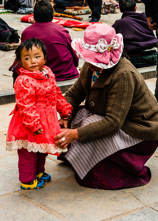 A mother smooths her daughter's dress in front of Jokhang Temple.