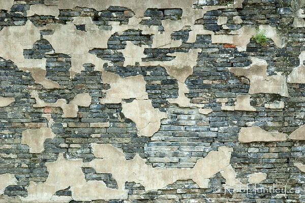 Stucco crumbling on a stone wall in Wuzhen, China.