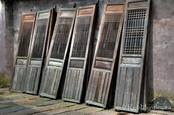 Row of wooden doors in a row awaiting repair. Wuzhen, China.