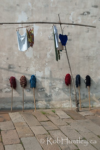 Laundry and mops. Wooden pole rack holding laundry and mops against a stucco wall. Wuzhen, China. © Rob Huntley