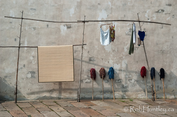 Laundry, mops and mat. Wooden pole rack holding laundry and a mat. Mops against a stucco wall. Wuzhen, China. © Rob Huntley