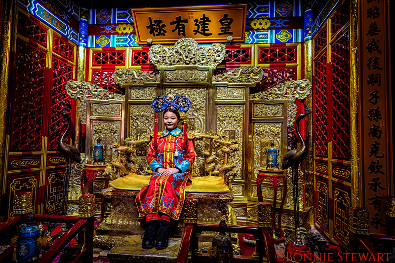 Young visitor to the Forbidden City poses in traditional costume in a Photo-Booth designed to give visitors a feel for the Royal Life of the past.