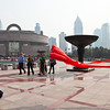 A man flies a kite in front of the Shanhai Museum.