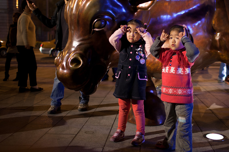 Young girls imitate the bull sculpture beside them for their parents to take a photo.