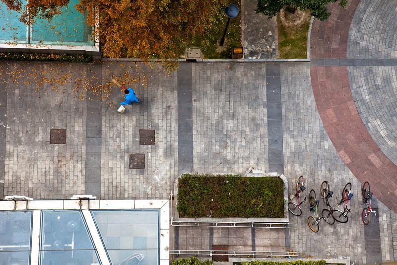 Sweeping away the leaves below my hotel room in Shanghai.