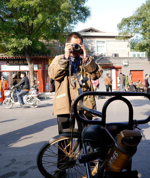 Beijing.  Our rickshaw driver takes our photo with our cameras.