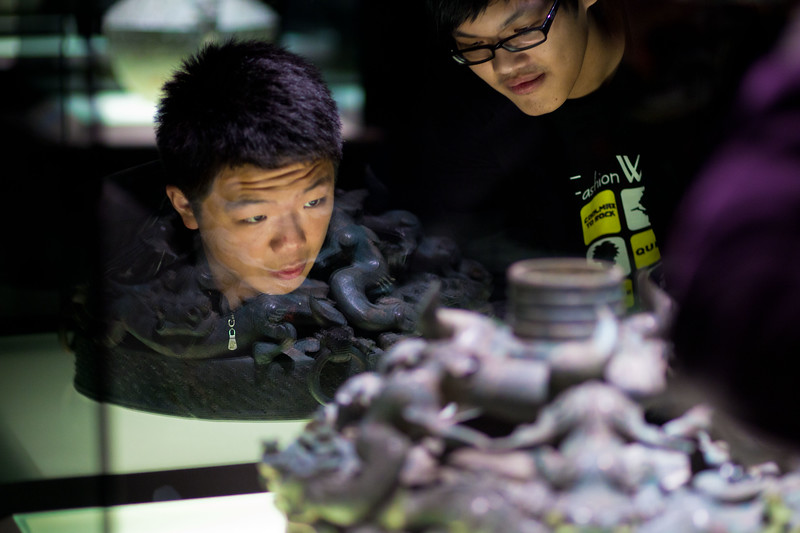 Visitors examine a bronze casting from about 300 BC.