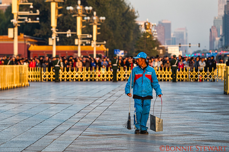 Guard sweeping the grounds in front of the Parliament  buildings facing Tiananmen Square before the changing of the guard.