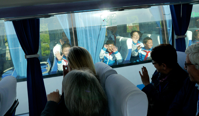 Beijing. We pass a bus full of kids and they see us and they all start waving and we wave back.