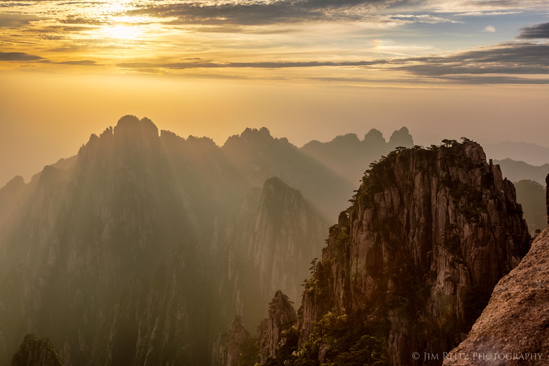 The setting sun casting rays down into the Xihei Grand Canyon, a couple thousand feet below - in Huangshan.