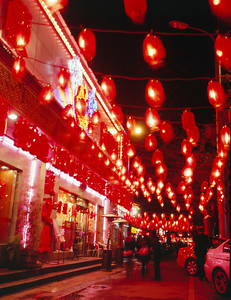 Ancient tradition meets modern technology. The entire street block is awash in light from red lanterns. Yet, they all are powered by compact florescent bulbs, and accented by neon signs. A beautiful sight. Beijing, China.