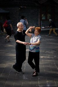 An older couple dancing all to themselves, among the huge crowds at Beijing's Summer Palace.