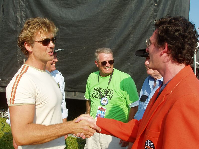 """John """"Bo Duke"""" Schneider congratulates Vice President, CMT Dukes of Hazzard Institute Christopher Nelson backstage at CMT DukesFest 2005 on Saturday, June 4, 2005 at the Bristol Motor Speedway and Dragway. Nelson's first official act as VP was presenting the Special Olympics of Arkansas with a $10,000 check from the CMT Dukes of Hazzard Institute. The Dukes of Hazzard airs 7 amd 11 pm ET/PT weeknights on CMT: Country Music Television. Photographer: Dan Smigrod"""