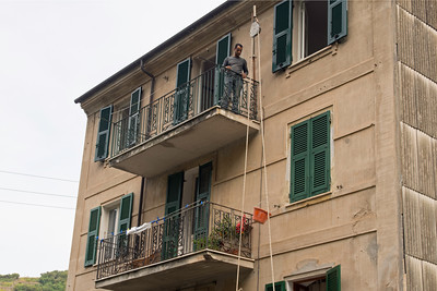Man in house in Manarola using hoist to move construction materials