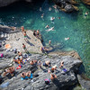 People relaxing in Manarola rocky bay, Manarola, Cinque Terre, Italy