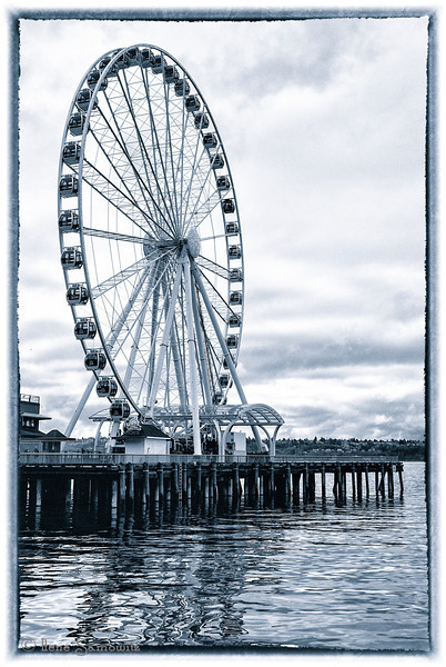 1-25-13 Ferris Wheel at Seattle Waterfront - I love photographing this wheel  It lends itself to many interesting compositions.  I took this on my lunch break when I got a chance to walk around.  The weather was close to 50 partly cloudy and no wind.  It was a very welcome respite from our recent weather.  It's due to start raining again but at least the temps will be above freezing.