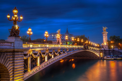 The Pont Alexandre III is an arch bridge that spans the Seine, connecting the Champs-Élysées quarter and the Invalides and Eiffel Tower quarter, widely regarded as the most ornate, extravagant bridge in Paris. It is classified as a historical monument.  The bridge, with its exuberant Art Nouveau lamps, cherubs, nymphs and winged horses at either end, was built between 1896 and 1900. It is named after Tsar Alexander III, who had concluded the Franco-Russian Alliance in 1892. His son Nicholas II laid the foundation stone in October 1896. The style of the bridge reflects that of the Grand Palais, to which it leads on the right bank.  Equipment=Canon T3I Rebel Lens Used=Tamron AF 17-50mm F/2.8 XR Di-II LD SP Aspherical (IF) Zoom Lens Exposures=7 Location=Paris, France  Workflow= PhotoMatix 4.2 Adobe PhotoShop Cs6(Lightning Adjustments=4.0) Adobe Light room 5  Software, Nik Color Efex=Tonal Contrast   OnOne Perfect Photo Suite=Angel Glow