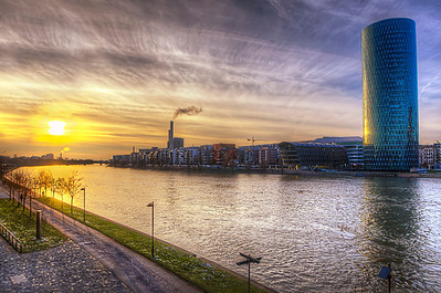 """Westhafen Tower is a 109.9 m (361 ft) 30-storey skyscraper in the Gutleutviertel district of Frankfurt, Germany. The building was designed by the architects Schneider & Schumacher and was completed in 2004. The tower, whose name literally means """"West Port Tower"""", is one of the first buildings at the former West Port.  From the outside, the building is shaped like a cylinder, but the storeys are square-shaped, creating 18 conservatories between the interior and exterior. Each of the 30 floors above ground has a rentable area of approximately 820 square metres. One of the architectural features is the rhomboid facade structure, with 3556 triangular panes of glass forming the outer skin.  The structure of the building's glass facade resembles the rhombic surface of a typical Frankfurtian cider glass. Therefore, the building is popularly called das Gerippte, literally meaning """"the Rhombic"""".  A portion of the triangular segments of the glass can be automatically opened for ventilation purposes in the bottom corner. The floors are heated with under the windows recessed convectors as the cooling is done via a cooling ceiling.  Equipment=Nikon D7000 Lens Used=Tamron SP AF 10-24mm F/3.5-4.5 Lens Exposures=3 Location=Frankfurt Germany  Workflow= PhotoMatix 4.2 Adobe PhotoShop Cs6 Adobe Light room 4.1 Software, Nik Color Efex=Cross Balance, Polarization and SkyLight  Topaz Details 3"""