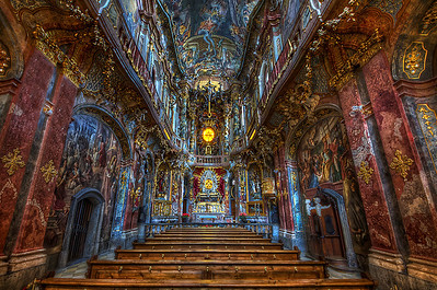 St. Johann Nepomuk, better known as the Asam Church (German: Asamkirche) is a church in Munich, southern Germany, built from 1733 to 1746 by the brothers Egid Quirin Asam and Cosmas Damian Asam as their private church. Due to resistance of the citizens, the brothers were forced to make the church accessible to the public. The church is considered to be one of the most important buildings of the main representatives of the southern German Late Baroque.  The church was built without an order, and as a private chapel for the greater glory of God and for the salvation of the builders. This allowed the brothers also to build in line with the ideas of independent contractors. So for example Egid Quirin Asam could watch the altar through a window of his private house next to the church (Asamhaus). Egid Quirin Asam designed the church as Beichtkirche (confession church) for the youth. So the small churchs has got seven confessionals with allegorical scenes.  The Baroque façade is integrated into the houses of the Sendlingerstraße and swings slightly convex outward. St. Johann Nepomuk was built in a confined space, the property is just 22 to 8 m. So even more astonishing is the performance of the two builders who were able to unite in the two-story space architecture, painting and sculpture in harmony. Especially the indirect lighting in the choir area is very well done: hidden behind the cornice window the Trinity figures are illuminated effective from behind. The cornice itself seems to swing up and down on its curved construction.  The interior is divided vertically into three sections, which increase in brightness from the bottom upwards. The lowermost portion of the benches for the church visitors is kept relatively dark and in the design symbolizes the suffering of the world. The second section, located above, is kept white and blue, and reserved for the emperor. The uppermost portion of the indirect and hidden illuminated ceiling painting is dedicated to God and eternity.   Equipment=Nikon D7000 Lens Used=Tamron SP AF 10-24mm F/3.5-4.5 Lens Exposures=7 Location=Munich Germany  Workflow= PhotoMatix 4.2 Adobe PhotoShop Cs6 Adobe Light room 4.1 Software, Nik Color Efex=Glamor Glow, and Detail Extractor   Topaz Details 3