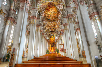 Heiliggeistkirche is a Gothic hall church in Munich, southern Germany, originally belonging to the Hospice of the Holy Ghost (14th century). It was remodeled in 1724-30 by Johann Georg Ettenhofer (vaults, renovation of pillars); in the interior are Rococo frescoes and stucco ornament by the Asam brothers. After the demolition of the hospice buildings in 1885, Franz Lšwel added three bays at the west end of the church and gave it a Neo-Baroque facade. The church suffered severe damage during World War II and its interior furnishings were largely destroyed; extensive rebuilding and restoration was carried out after the war.  Of the original Gothic church only the choir buttresses and the north wall of the nave remain.  The tower (1730) has a lantern dome of characteristic Munich type. The Neo-Baroque facade shows use of elements borrowed from Viscardi's Trinity Church.  The interior is aisled, with an ambulatory round the choir. The nave is barrel-vaulted, with small vaults over the windows. The aisles have groined vaulting.  Among several items of art-historical interest in the church are: in the portico, to left and right of the main entrance, parts of a bronze memorial made in 1608 by Hans Krumpper for Duke Ferdinand of Bavaria, Infante of Spain; in the chancel, the high altar by Nikolaus Stuber (1730), with an altarpiece by Ulrich Loth depicting The Effusion of the Holy Ghost (1661) and two flanking figures of angels by Johann Georg Greiff (1729); in the right aisle, a series of wall paintings (1725) by Peter Horeman illustrating the Seven Gifts of the Holy Spirit; in the Kreuzkapelle, a late Gothic crucifix (1510); and, midway along the left aisle, an altar with an allegedly miraculous image of the Hammerthaler Madonna (15th century).  The interior of the church was renovated in 1991.  Equipment=Nikon D7000 Lens Used=Tamron SP AF 10-24mm F/3.5-4.5 Lens Exposures=7 Location=Munich Germany  Workflow= PhotoMatix 4.2 Adobe PhotoShop Cs6 Adobe Light room 4.1 Software, Nik Color Efex=Glamor Glow, Tonal Contrast, Pro Contrast, and Detail Extractor  Topaz Details 3