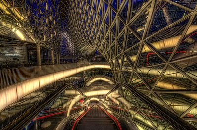 The MyZeil is a shopping mall in the city center of Frankfurt, designed by Roman architect Massimiliano Fuksas. It is part of the building ensembles PalaisQuartier and forms its access to the Zeil shopping street. It was officially opened on 26 February 2009, during a public presentation of Frankfurt's Mayor Petra Roth and recorded 120,000 visitors on the first day, according to press reports. Because of massive interest, visitors had to be admitted in phases; after two weeks, visitors exceeded the one million mark.  The MyZeil has six floors, with one of the longest escalators in Germany (46 m). The gross floor under the vaulted structure of about 3,200 triangular glass surfaces is 77,000 square metres. The retail area on the bottom three floors account for about 52,000 square metres. The anchor tenants include a Rewe-Markt (food), Anson's (menswear with many leading fashion labels), as well as Saturn (electronics and home appliances market). In the upper floors, there is a 'gastro-boulevard' area with restaurants, a fitness club (Fitness First), and games and care for children. On opening, of the nearly 100 shops, about 97 percent were rented out when the mall opened. The square metre price was expected to amount to a record high of up to 485 euros.  The structural design of the imposing steel and glass construction is by Knippers Helbig from Stuttgart. Rainwater from the nearly 6000 square meters large roof areas is collected, cleaned and returned to the water cycle of the house. Early 2008, the shell of the shopping center was completed and the interior work started.  Equipment=Nikon D7000 Lens Used=Tamron SP AF 10-24mm F/3.5-4.5 Lens Exposures=7 Location=Frankfurt Germany  Workflow= PhotoMatix 4.2 Adobe PhotoShop Cs6 Adobe Light room 4.1 Software, Nik Color Efex=Brilliance/Warmth, Tonal Contrast, and Glamor Glow  Topaz Adjust 5=Photo Pop  OnOne Perfect Photo Suite 7=Deep Forest, and Dark Glow