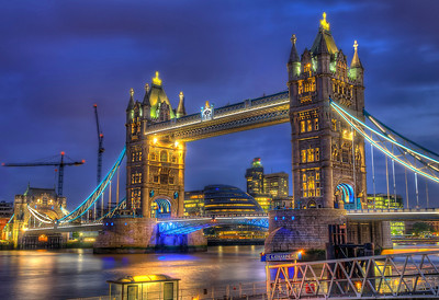"Tower Bridge (built 1886–1894) is a combined bascule and suspension bridge in London, over the River Thames. It is close to the Tower of London, from which it takes its name. It has become an iconic symbol of London.  The bridge consists of two towers tied together at the upper level by means of two horizontal walkways, designed to withstand the horizontal forces exerted by the suspended sections of the bridge on the landward sides of the towers. The vertical component of the forces in the suspended sections and the vertical reactions of the two walkways are carried by the two robust towers. The bascule pivots and operating machinery are housed in the base of each tower. The bridge's present colour scheme dates from 1977, when it was painted red, white and blue for the Queen Elizabeth II's silver jubilee. Originally it was painted a mid greenish-blue colour.  The nearest London Underground station is Tower Hill on the Circle and District lines, and the nearest Docklands Light Railway station is Tower Gateway.  Contrary to popular belief, the song ""London Bridge is Falling Down"" has nothing to do with Tower Bridge, instead referring to the collapses of other various London Bridges.  Equipment=Nikon D7000 Lens Used=Sigma 17-70mm f/2.8-4 DC Macro OS HSM Lens Exposures=7 Location=London England  Workflow= PhotoMatix 4.2 Adobe PhotoShop Cs6(Lightning Adjustments=-3) Adobe Light room 5 Software, Nik Color Efex=Tonal Contrast(Colors Only)  Nik Sharpener Pro 3.0  Topaz Adjust 5=Photo Pop  Topaz Clarity  OnOne Perfect Photo Suite 7=Angel Glow, and Dark Glow"