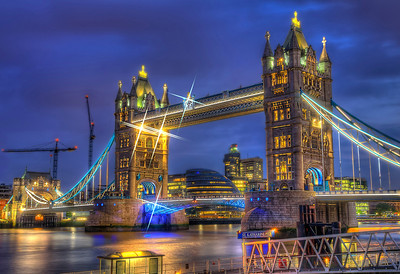 "Tower Bridge (built 1886–1894) is a combined bascule and suspension bridge in London, over the River Thames. It is close to the Tower of London, from which it takes its name. It has become an iconic symbol of London.  The bridge consists of two towers tied together at the upper level by means of two horizontal walkways, designed to withstand the horizontal forces exerted by the suspended sections of the bridge on the landward sides of the towers. The vertical component of the forces in the suspended sections and the vertical reactions of the two walkways are carried by the two robust towers. The bascule pivots and operating machinery are housed in the base of each tower. The bridge's present colour scheme dates from 1977, when it was painted red, white and blue for the Queen Elizabeth II's silver jubilee. Originally it was painted a mid greenish-blue colour.  The nearest London Underground station is Tower Hill on the Circle and District lines, and the nearest Docklands Light Railway station is Tower Gateway.  Contrary to popular belief, the song ""London Bridge is Falling Down"" has nothing to do with Tower Bridge, instead referring to the collapses of other various London Bridges.  Equipment=Nikon D7000 Lens Used=Sigma 17-70mm f/2.8-4 DC Macro OS HSM Lens Exposures=7 Location=London England  Workflow= PhotoMatix 4.2 Adobe PhotoShop Cs6(Lightning Adjustments=-3) Adobe Light room 5 Software, Nik Color Efex=Tonal Contrast(Colors Only)  Nik Sharpener Pro 3.0  Topaz Adjust 5=Photo Pop  Topaz Clarity  Topaz Stars  OnOne Perfect Photo Suite 7=Angel Glow, and Dark Glow"