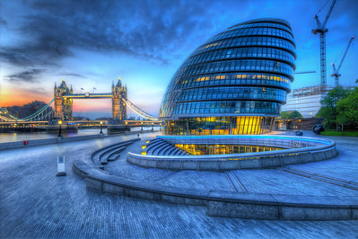 City Hall is the headquarters of the Greater London Authority (GLA) which comprises the Mayor of London and the London Assembly. It is located in Southwark, on the south bank of the River Thames near Tower Bridge. It was designed by Norman Foster and opened in July 2002, two years after the Greater London Authority was created.  City Hall was constructed at a cost of £43 million [4] on a site formerly occupied by wharves serving the Pool of London. The building does not belong to the GLA but is leased under a 25-year rent.[5] Despite its name, City Hall is neither located in nor does it serve a city (as recognised by English constitutional law), often adding to the confusion of Greater London with the City of London, whose headquarters is in the Guildhall, north of the Thames. In June 2011 Mayor Boris Johnson announced that for the duration of the London 2012 Olympic Games, the building would be called London House.  Equipment=Canon T3I Rebel Lens Used=Sigma 10-20mm f/4-5.6 EX DC HSM Lens Exposures=7 Location=London England  Workflow= PhotoMatix 4.2 Adobe PhotoShop Cs6(Lightning Adjustments=0) Adobe Light room 5 Software, Nik Color Efex=Glamor Glow, Tonal Contrast,Dynamic Skin Softener, and Brilliance/Warmth(Cold)  Nik Sharpener Pro 3.0  Topaz Details 3  OnOne Perfect Photo Suite 7=Dark Glow