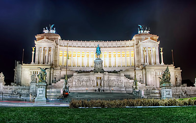 """The Altare della Patria (Altar of the Fatherland) also known as the Monumento Nazionale a Vittorio Emanuele II (National Monument to Victor Emmanuel II) or """"Il Vittoriano"""" is a monument built in honour of Victor Emmanuel, the first king of a unified Italy, located in Rome, Italy. It occupies a site between the Piazza Venezia and the Capitoline Hill. The monument was designed by Giuseppe Sacconi in 1885; sculpture for it was parceled out to established sculptors all over Italy, such as Leonardo Bistolfi and Angelo Zanelli.[1] It was inaugurated in 1911 and completed in 1925.  The monument is built of white marble from Botticino, Brescia, and features stairways, Corinthian columns, fountains, an equestrian sculpture of Victor Emmanuel and two statues of the goddess Victoria riding on quadrigas. The structure is 135 m (443 ft) wide and 70 m (230 ft) high. If the quadrigae and winged victories are included, the height is to 81 m (266 ft).  The base of the structure houses the museum of Italian Reunification. In 2007, a panoramic elevator was added to the structure, allowing visitors to ride up to the roof for 360 degree views of Rome."""