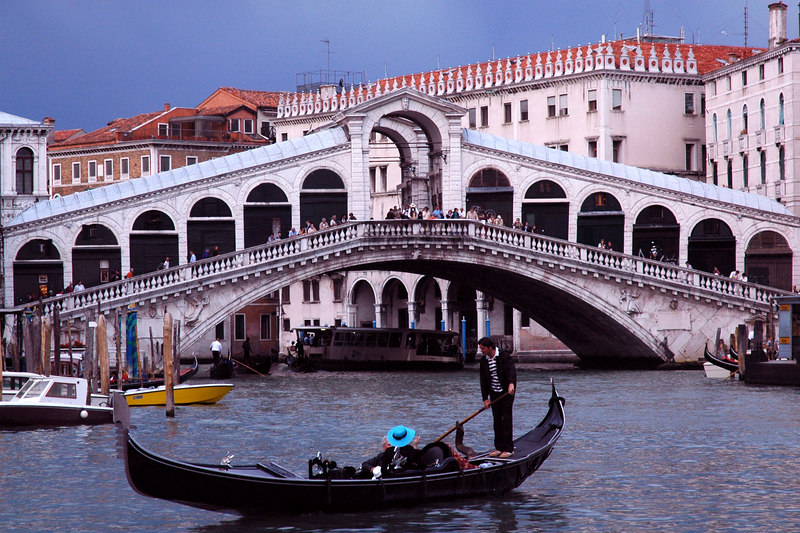 June 2nd, 2006.<br /> A gondolier paddles by the Rialto bridge on the grand canal.