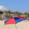 A colorful beach umbrella near a dune fence, Misquamicut, Rhode Island
