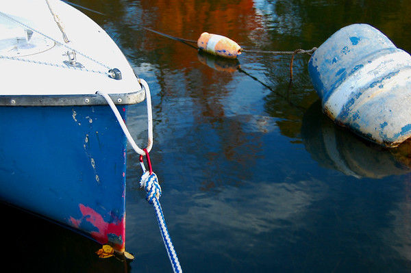 An old sailboat and buoys on a lake with autumn foliage reflected on the surface