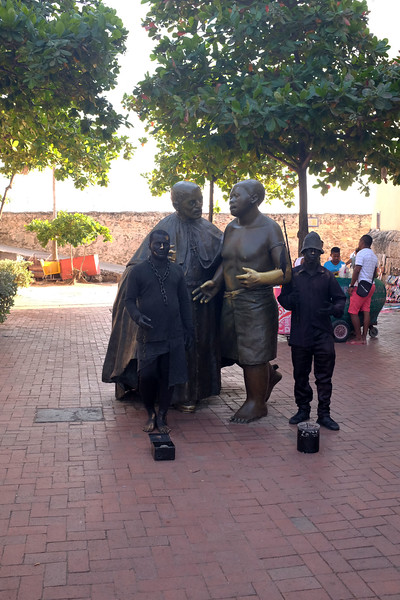 """The taller statues are part of a series of metal sculptures of people at work around the plaza. The shorter statues are performance art. Note the """"hats"""" for coins on the pavement."""