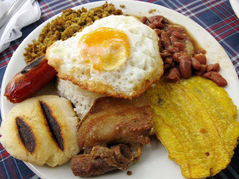 "Final morning's breakfast: bandeja paisa, a lovely Colombian bit-of-everything meal--famous for curing hangovers--which consists of ground beef, red beans, fried plantain, chicharron, arepa, chorizo, rice, and egg. This is actually a ""mini paisa""--imagine the full one at twice this size! (To its credit, the big one also includes a salad.)"