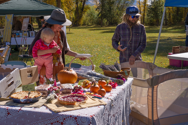 Young family selling produce and pie at a roadside farmer's market in Yampa, Colorrado.