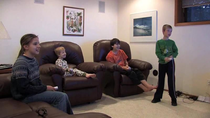Marissa, Joel, Dante, and Erik play tennis on the Wii in Grandma and Grandpa's basement