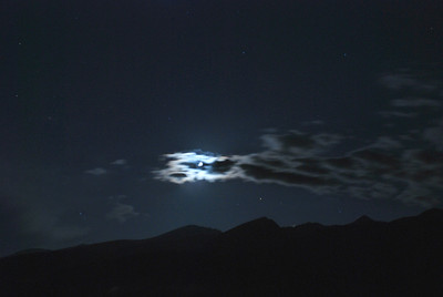 July 31, Breckenridge.   Time lapsed photo of moon illuminating the slow moving clouds.  Stars and the outlines of the Breckenride ski-run mountains are shown.