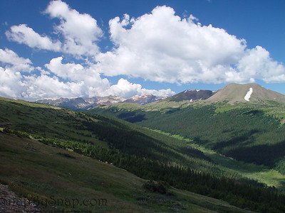 A long green valley and white fluffy clouds in Rocky Mountain National Park.