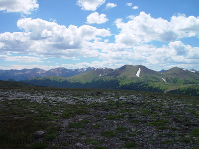 Looking across the alpine tundra to the mountains in the distance with puffy white clouds in Rocky Mountain National Park.