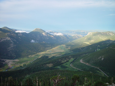A road meandering down the side of a mountain and into a valley in Rocky Mountain National Park.