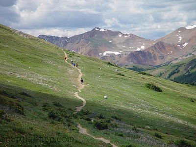 A trail leading into the high mountains with hikers in Rocky Mountain National Park.