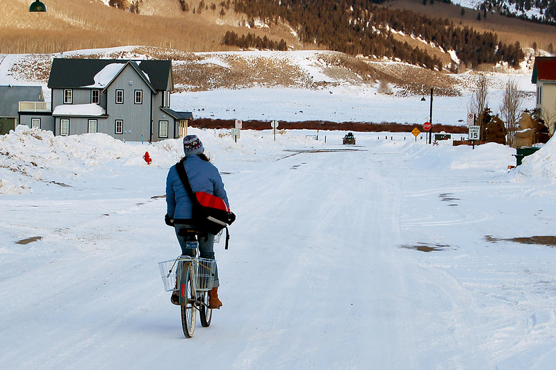 Woman biking down snowcovered street, Crested Butte, CO