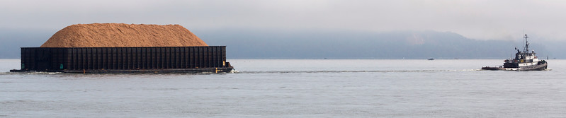 Small tug boat: Large wood-chip-filled barge