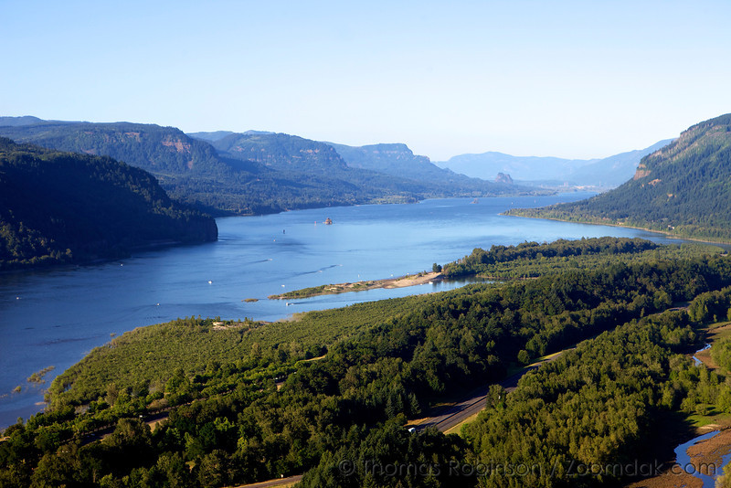 The Columbia River Gorge abounds with life and activity on a sunny summer day. From Crown Point, one can see Rooster Rock State Park in the foregroun and Beacon Rock poking up in the background.