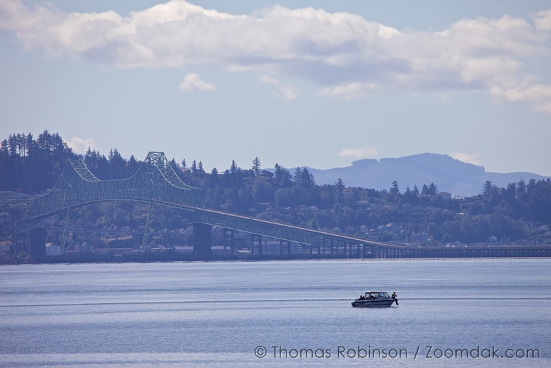 A couple of guys fish from thier boat in the middle of the Columbia River with Astoria-Megler Bridge in the background.