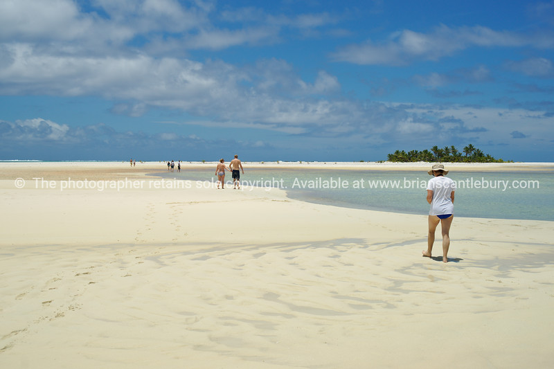 """Exploring, tourists exploring an exposed coral sandband while the tide is low. Cook Islands, Aitutaki. Please preview book """"Cook Islands"""", above.  <a href=""""http://www.blurb.com/b/1907535-cook-islands"""">http://www.blurb.com/b/1907535-cook-islands</a>"""