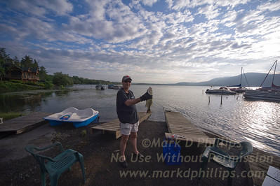 Lake Otsego fishing from the lakeside at the Lake N Pines Motel in Cooperstown, New York for travel story. Mark D Phillips with Large Mouth Bass