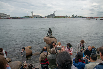 Big crowds gather around the small area and the small statue of the mermaid. The Little Mermaid, Den Lille Havfrue, Langelinie, København, Copenhagen, Denmark. Iconic bronze mermaid sculpture, by Edvard Eriksen, of a character from H.C. Andersen's fairytale.